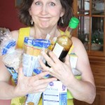 Jennifer Cote displays common GMO groceries: Pasta, Sugar, Rice, Tomatoes, Soy